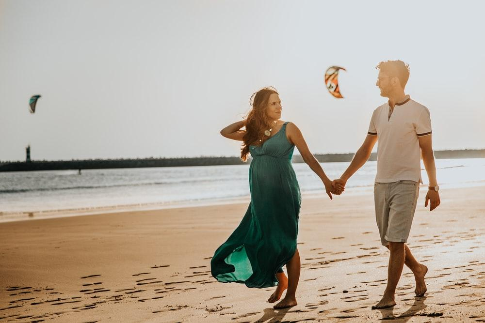 pregnant woman and man walking on beach
